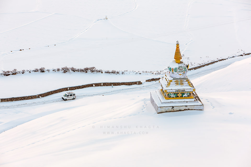 A car driving on snow covered road passes through a chorten near Rangrik village of Spiti. Picture by Himanshu Khagta
